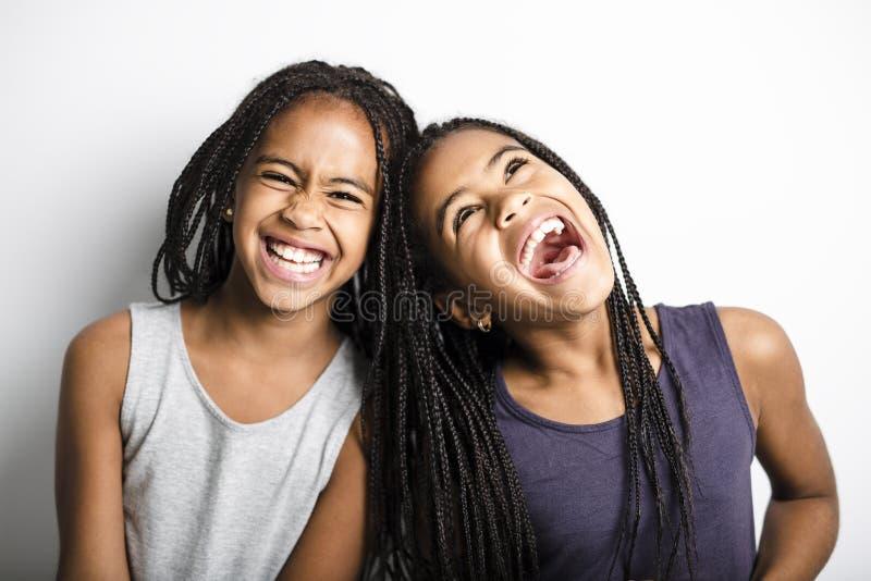 Grånar tvilling- små flickor för förtjusande afrikan på studio bakgrund royaltyfri bild
