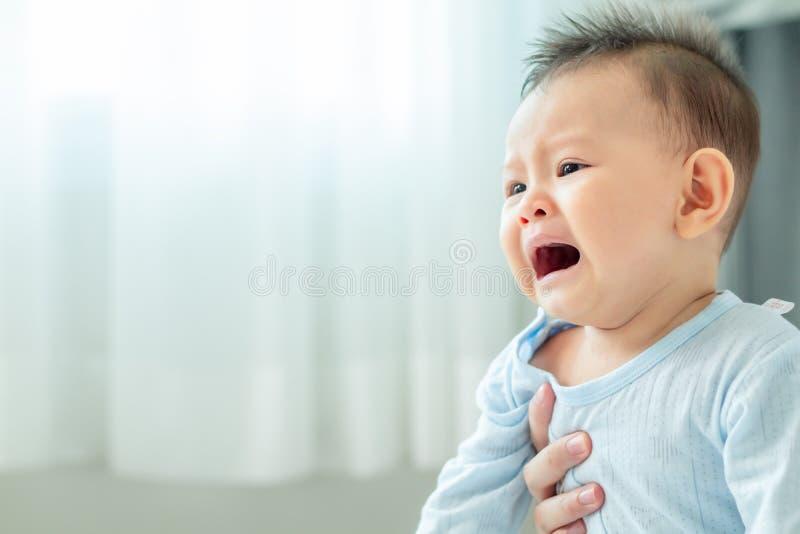 Gråt behandla som ett barn i hans moders hand i sovrum royaltyfria foton