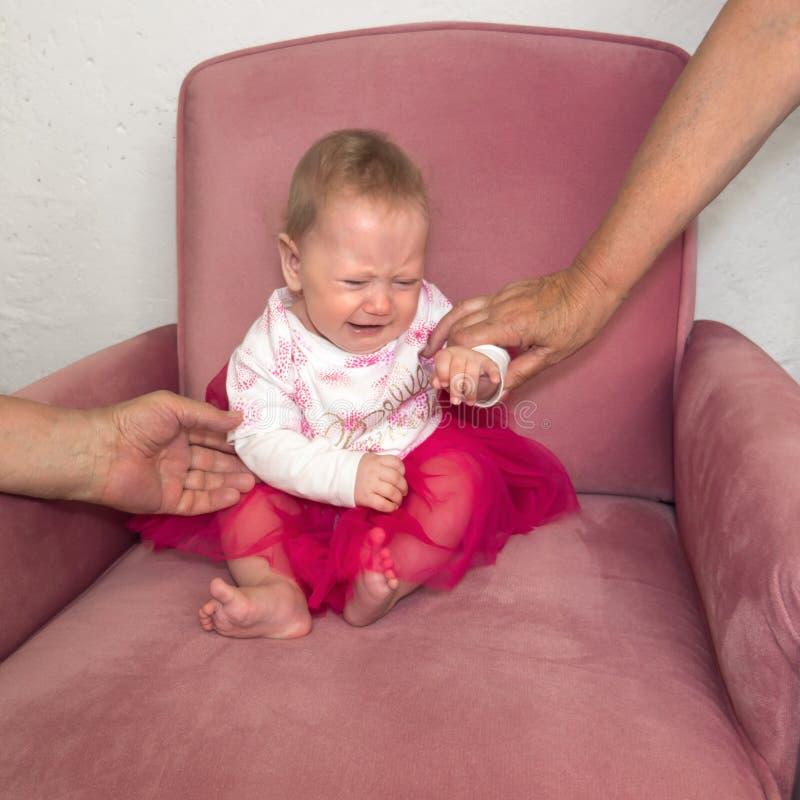 Gråt behandla som ett barn sammanträde i stolen Händer av farmorinnehavbarnet som sitter i stolen Negativ barnsinnesrörelse royaltyfri fotografi