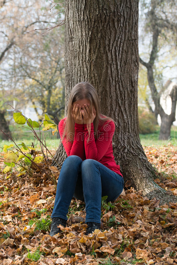 Gråt för ung kvinna i hösten parkerar arkivfoto