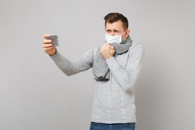 Gråta den unga mannen i grå tröja, för framsidamaskering för halsduk som sterilt samtal gör den videopd appellen med mobiltelefon royaltyfria foton