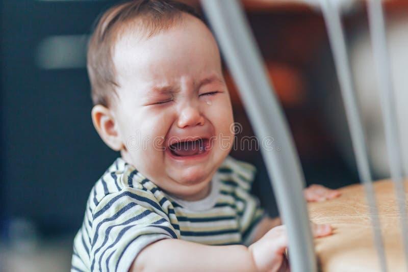 Gråta denhaired flickan för liten cutie, står gråta högt och att stå nära stol hemma fotografering för bildbyråer