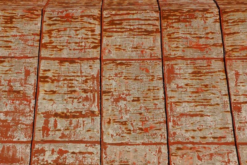 Grått gammalt järn är rött på taket av den lantliga boningshuset arkivbilder