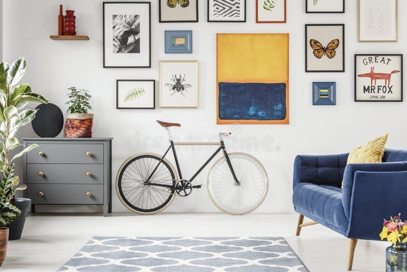 Grått kabinett bredvid cykeln i plan inre med den blåa soffan, gummin royaltyfria foton