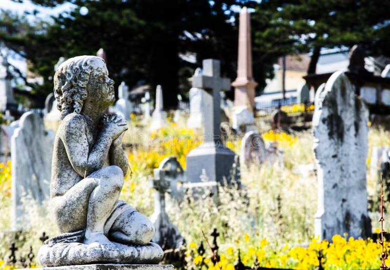 Grått sammanträde för stenpojkestaty och be på en kyrkogård royaltyfri bild