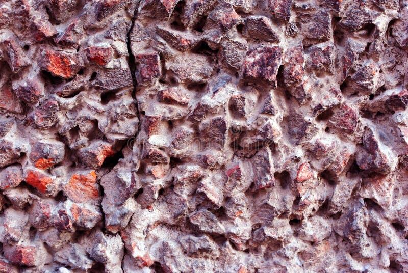 Grått texturerat stenigt yttersidaslut upp detaljen, den rosa krossade stenen och grå betong, grungehorisontalbakgrund arkivfoto