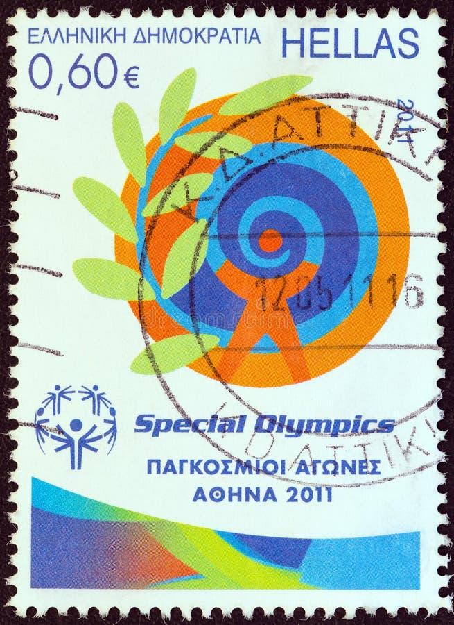 GRÉCIA - CERCA DE 2011: Um selo impresso em Grécia 'do emblema das mostras da edição de Atenas 2011 dos jogos de mundo dos Olympi imagem de stock