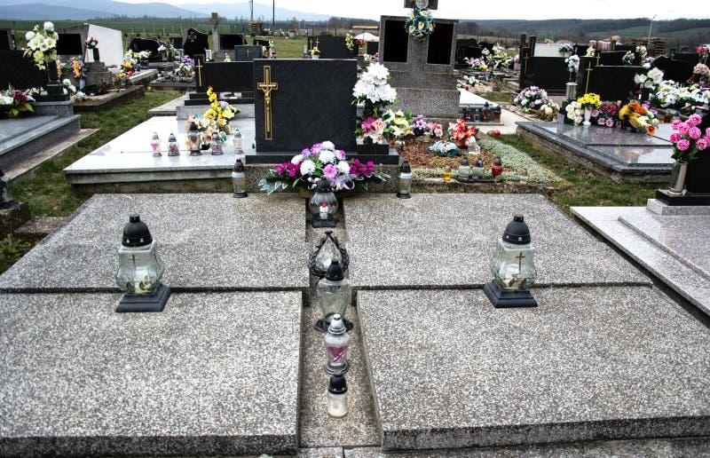 Grób, nagrobki i krucyfiksy na tradycyjnym cmentarzu, Wotywne świeczki lampionu i kwiaty na grobowcowych kamieniach w cmentarzu fotografia stock