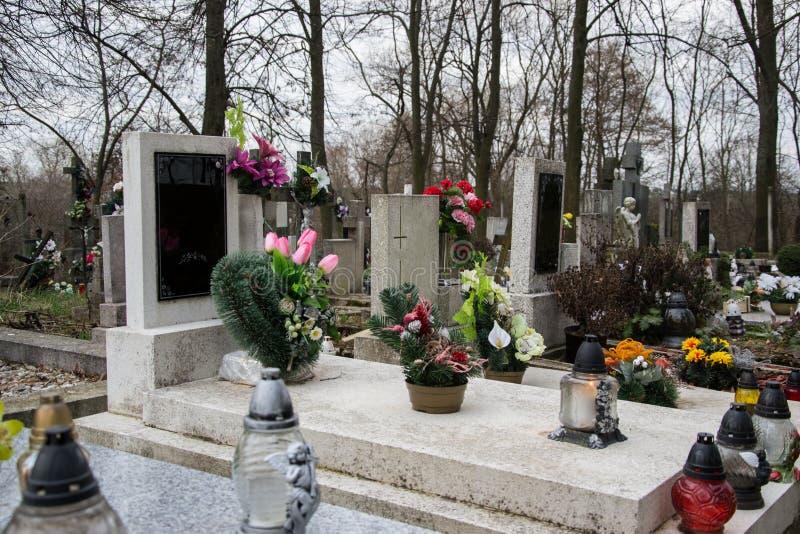 Grób, nagrobki i krucyfiksy na tradycyjnym cmentarzu, Wotywne świeczki lampionu i kwiaty na grobowcowych kamieniach w cmentarzu obraz royalty free