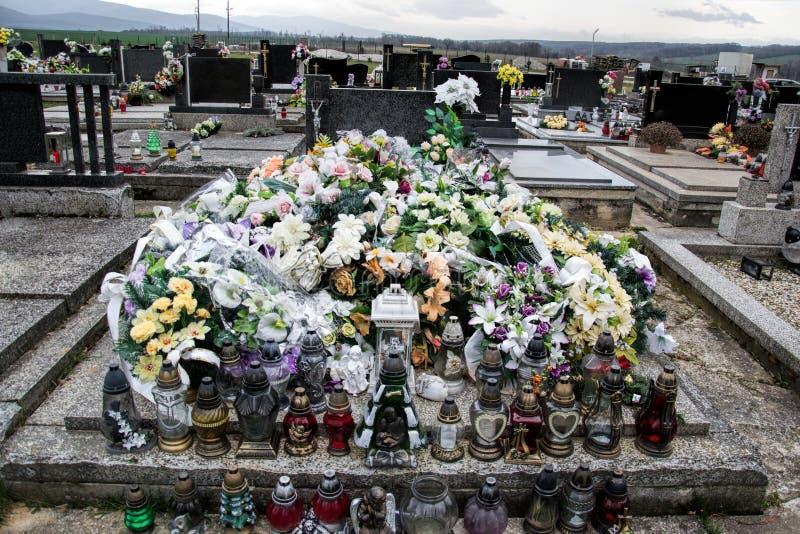 Grób, nagrobki i krucyfiksy na tradycyjnym cmentarzu, Wotywne świeczki lampionu i kwiaty na grobowcowych kamieniach w cmentarzu zdjęcia stock