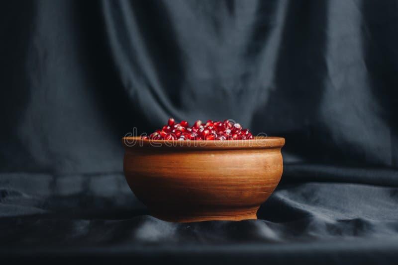 Grões da romã em uma bacia cerâmica em um fundo preto da tela, fruto da romã, jarro cerâmico, placa cerâmica, isolada ainda imagem de stock royalty free