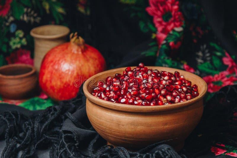 Grões da romã em uma bacia cerâmica em um fundo da tela do vintage, fruto da romã, jarro cerâmico, placa cerâmica, xaile étnico, imagem de stock