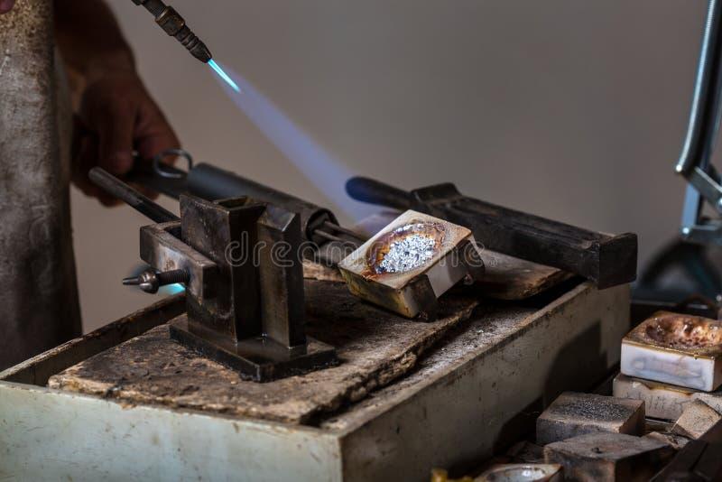 Grões de prata de derretimento ao estado líquido no cadinho fotografia de stock