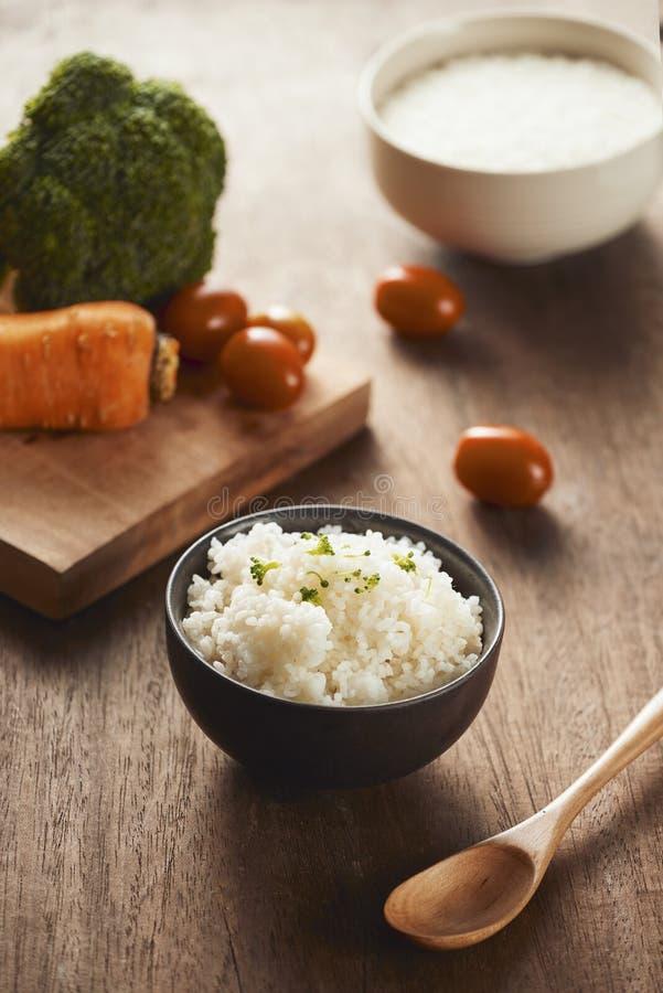 Grões do arroz em uma bacia de madeira e em ingredientes para uma receita do vegetariano - conceito saudável comer fotos de stock