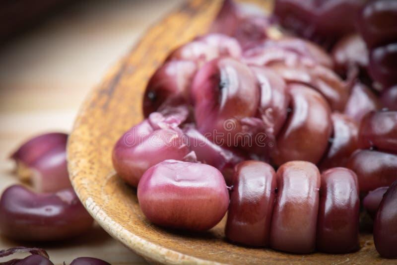 Grões roxas do milho na colher de madeira fotos de stock royalty free