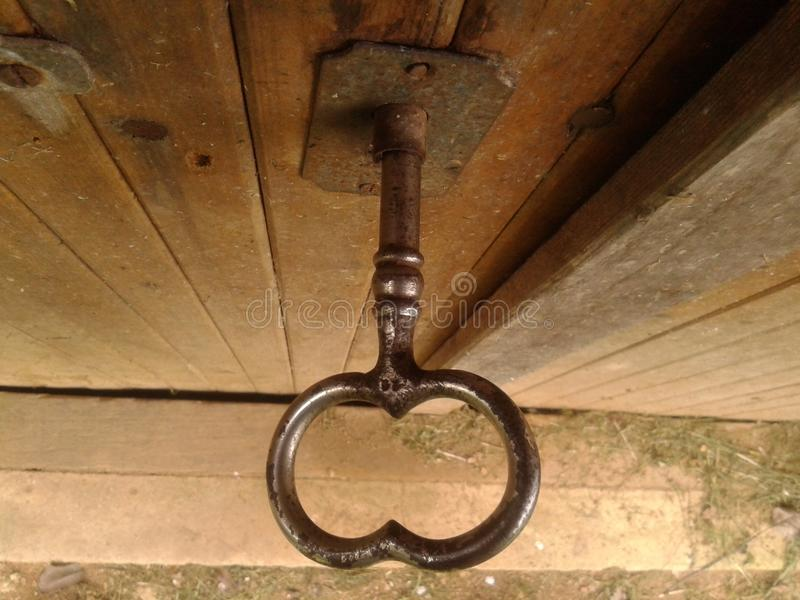 Größerer alter getragener schwarzer glänzender Schlüssel in der hölzernen staubigen Kellertür der Eiche, Nahaufnahme von oben, im stockbilder