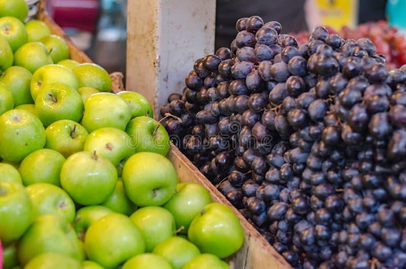 Grön äpple- och druvabakgrundsskärm på nytt stånd royaltyfria foton