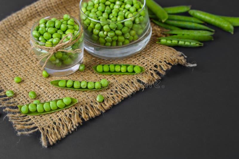 Grön ärta i exponeringsglas, ärtafröskidor, spridd ärta, på svart bakgrund royaltyfria bilder