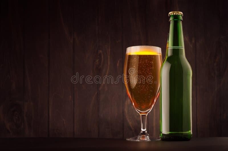Grön ölflaska- och exponeringsglastulpan med guld- lager på det wood brädet för mörk brunt, kopieringsutrymme, åtlöje upp royaltyfria foton