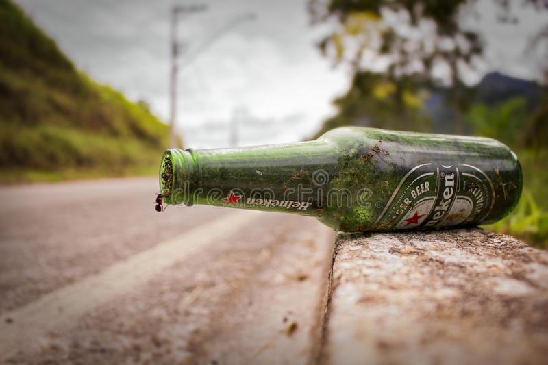 Grön ölflaska på trottoarkanten royaltyfri foto