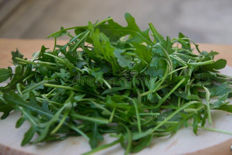 Grön arugula lämnar på träskärbräda Ny rucola i köket i det plast- magasinet, italiensk smaktillsats Sund livsstil arkivfoto