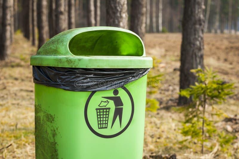 Grön avfallkorg i skog. fotografering för bildbyråer