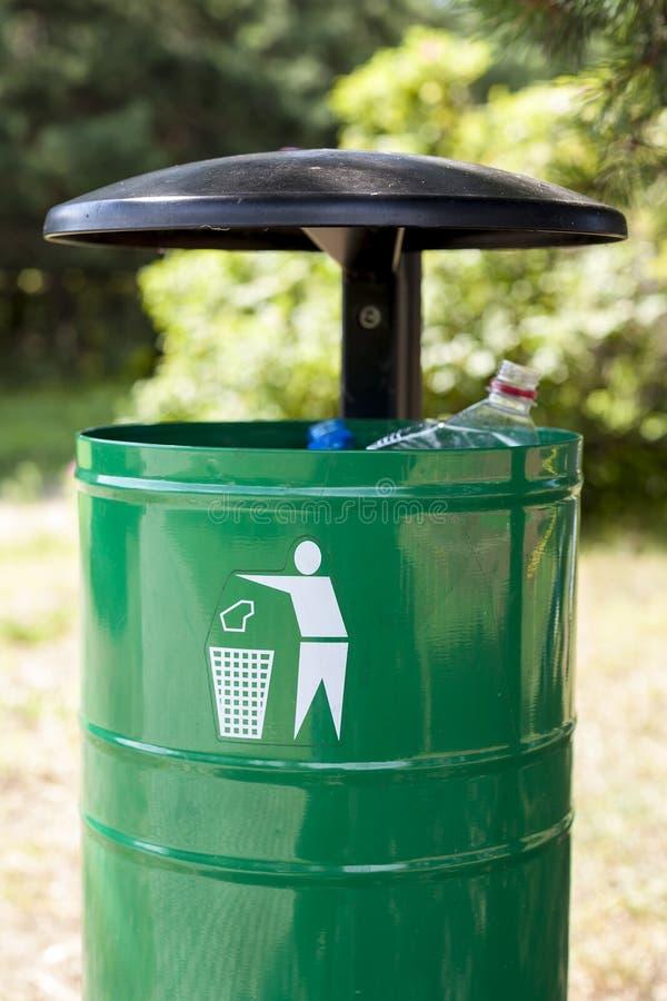 Grön avfallkorg med teckenpictogramen. royaltyfri fotografi