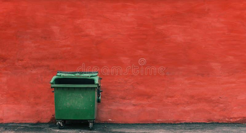 Grön avskrädebehållare på en röd väggbakgrund arkivfoto