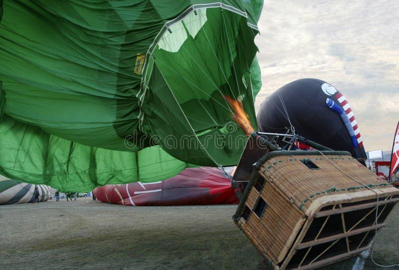 Grön ballong för varm luft, korg på jordningen, flamma på gasbrännaren arkivfoton