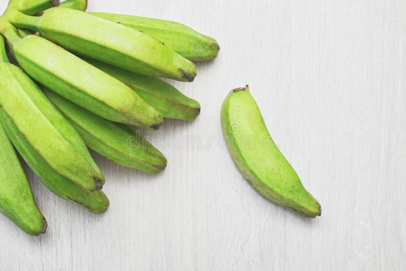 Grön banan på en lantlig trätabell arkivbilder