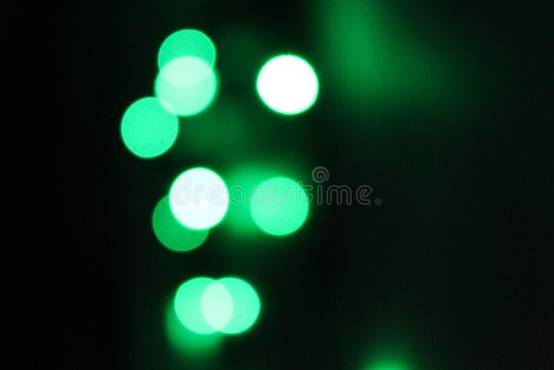 Grön bokeh för abstrakta ljus och vita signaler på svart bakgrund royaltyfri bild