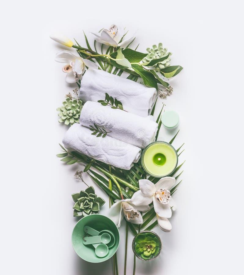 Grön brunnsort eller wellness som komponerar med handdukar, stearinljus, tropiska sidor arkivfoton