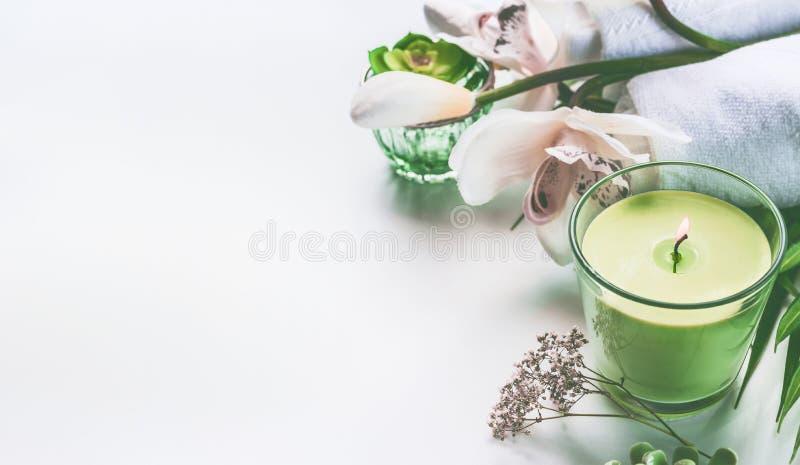 Grön brunnsort- eller wellnessbakgrund med handdukar, stearinljuset, orkidéblommor och tillbehör arkivfoto