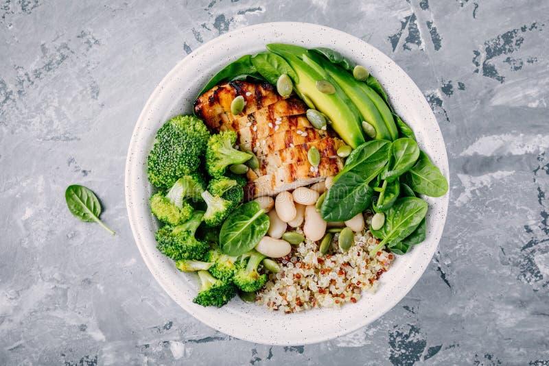 Grön buddha bunkelunch med grillad höna och quinoa, spenat, avokado, broccoli och vita bönor arkivfoto