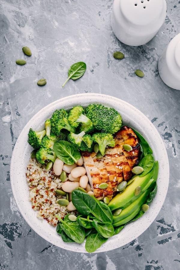 Grön buddha bunkelunch med grillad höna och quinoa, spenat, avokado, broccoli och vita bönor fotografering för bildbyråer