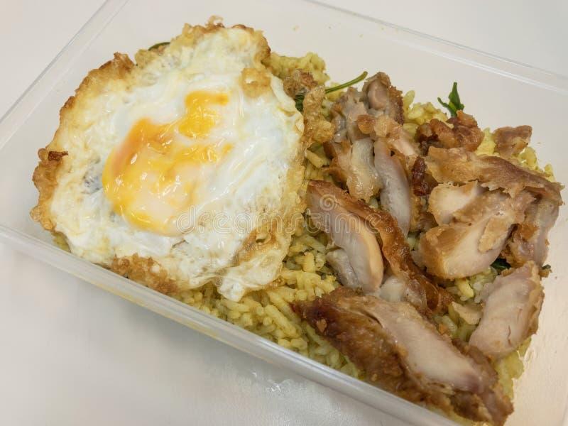 Grön curry stekte ris med stekt kyckling och stekte ägget i en ask thai mat royaltyfri foto