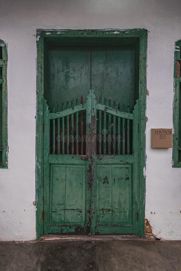 Grön dörr i gammalt hus arkivbilder