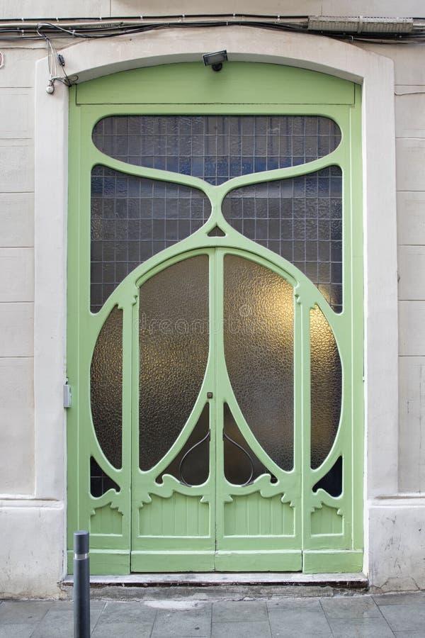 Grön dörr med en romantisk blomma som modernistisk garnering i Gracia, Barcelona, Spanien royaltyfria foton