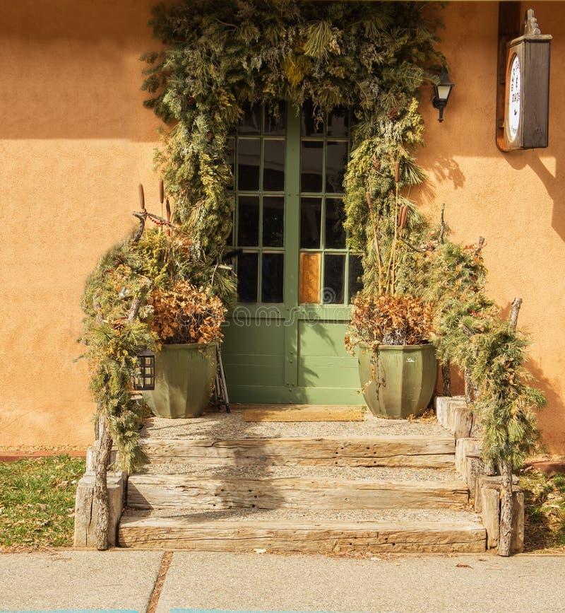 Grön dörr som inramas av grön lövverk royaltyfria bilder