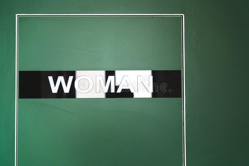Grön dörr till toaletten med en inskriftkvinna arkivbild