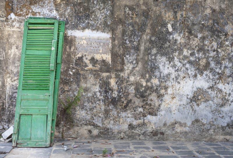 Grön dörrbenägenhet mot väggen royaltyfri bild