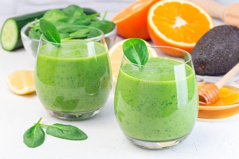 Grön detox smoothie med avokado, spenat, gurka, orange, citron och honung, horisontell arkivfoton