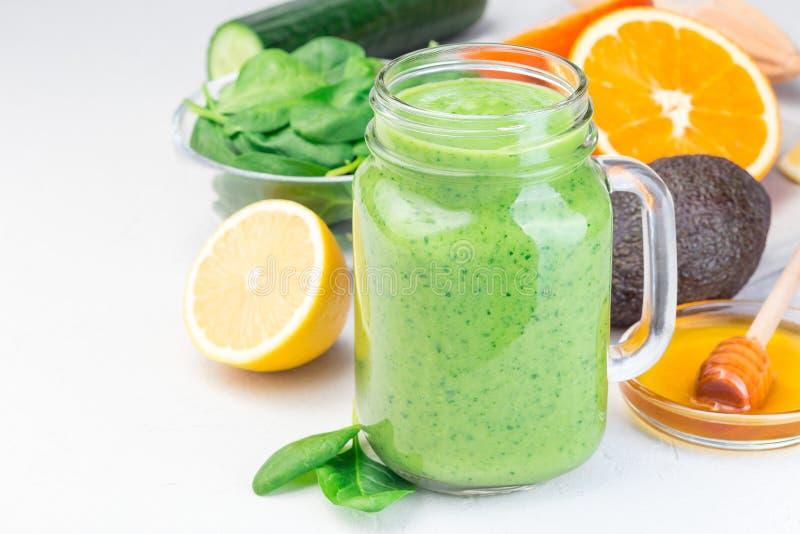 Grön detox smoothie med avokado, spenat, gurka, orange, citron och honung, i glasburk, horisontell, kopieringsutrymme, förslutnin arkivbilder