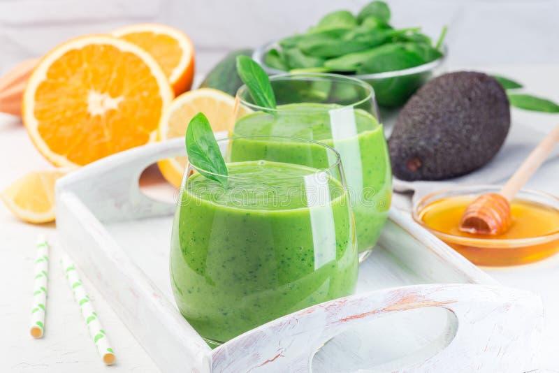 Grön detox smoothie med avokado, spenat, gurka, orange, citron och honung, på träbrickor, horisontell royaltyfri foto