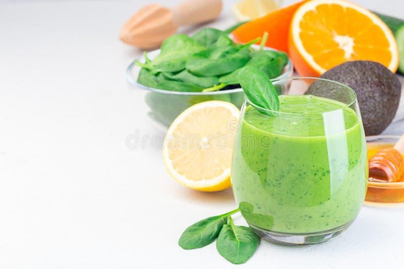 Grön detox smoothie med avokado, spenat, gurka, orange, citron och honung, vågrätt, kopieringsutrymme arkivbild