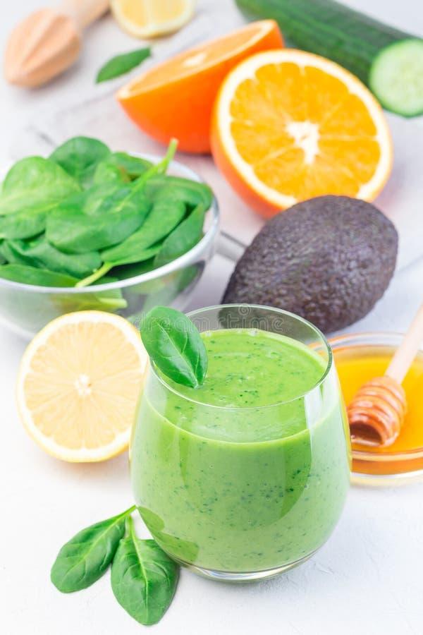 Grön detox smoothie med avokado, spenat, gurka, orange, citron och honung, vertikal fotografering för bildbyråer