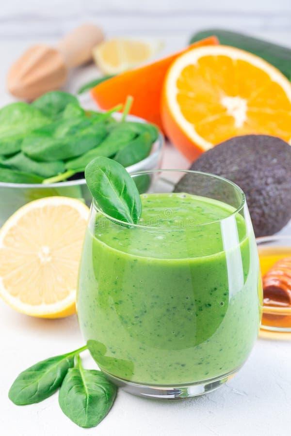 Grön detox smoothie med avokado, spenat, gurka, orange, citron och honung, vertikal royaltyfri fotografi