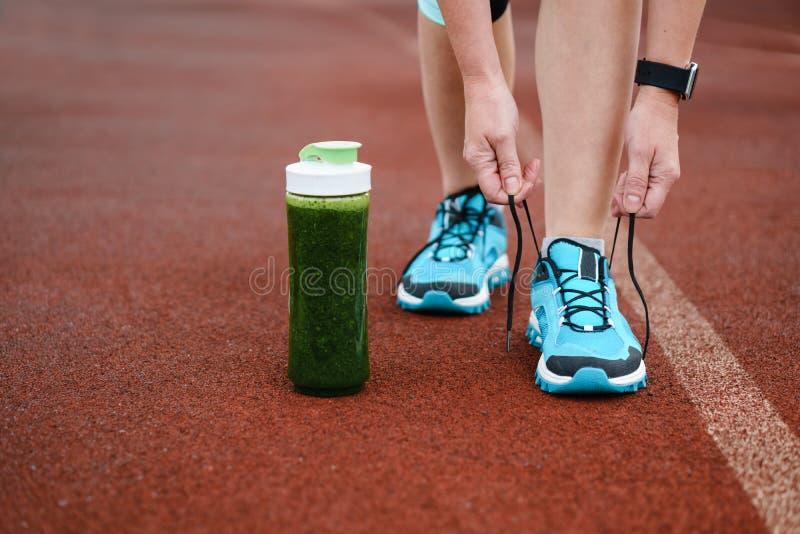 Grön detoxsmoothiekopp och kvinna som snör åt rinnande skor för w royaltyfria foton