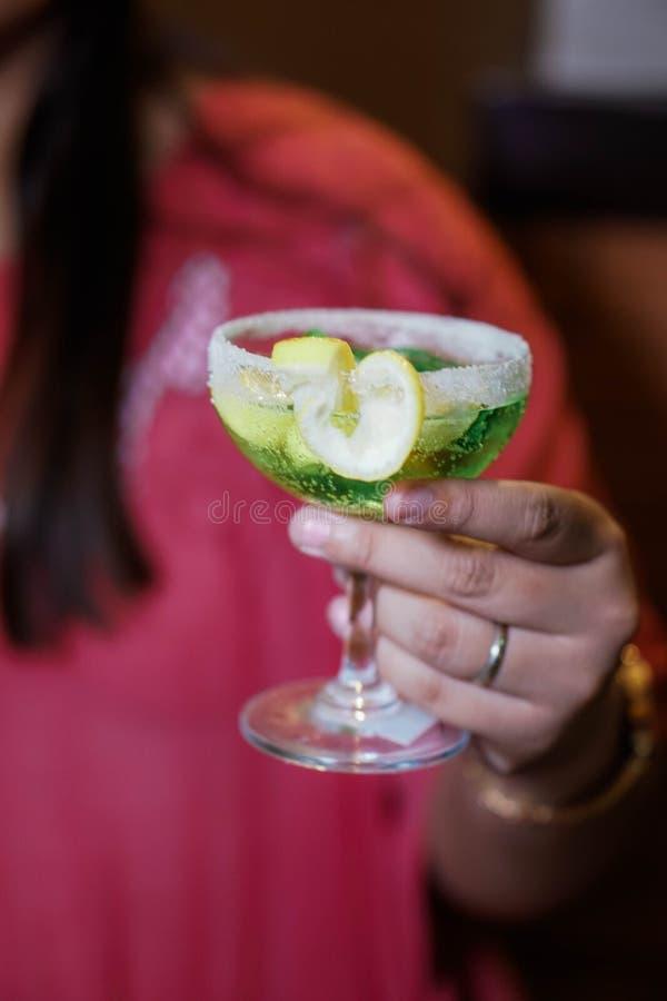 Grön drink på ett exponeringsglas royaltyfri bild