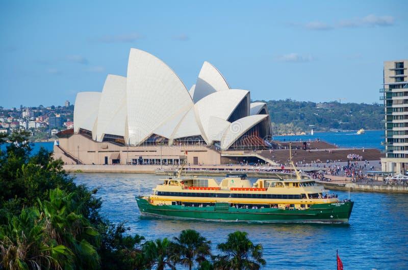 Grön färja i den Sydney hamnen med operahuset på bakgrunden arkivbild